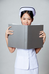Young Asian nurse smile with a folder