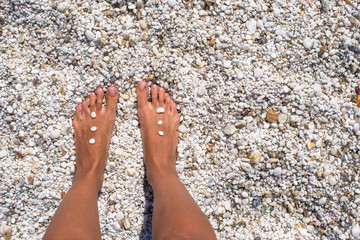 Close up of female legs with pebbles on white sandy beach