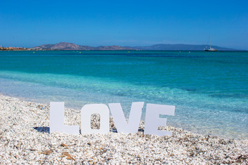 Word love on tropical beach background of the turquoise sea and