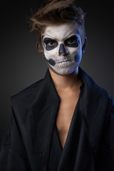 Teen with make-up of skull in black cloak unhappy