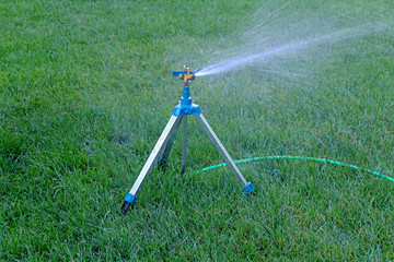 Mobile sprinkler system mounted on tripod working on fresh green