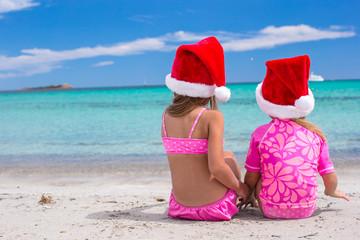 Little adorable girls in Santa hats during their beach tropical
