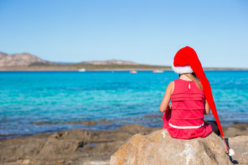 Adorable little girl in Santa hat and red dress sitting on big
