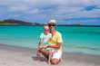 Young father and little daughter sitting on tropical white sand