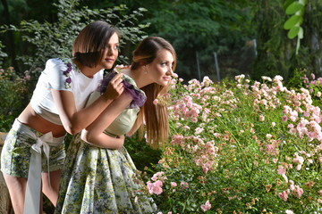 Pretty young women models smelling flowers in park