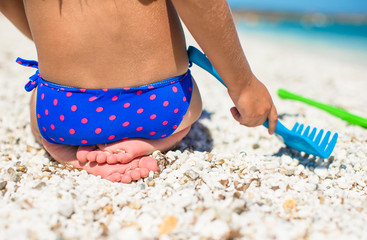 Closeup of little girl legs on tropical beach with toys
