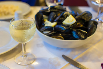 Mussel with white wine sauce at plate on table