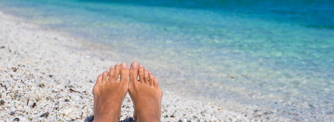 Closeup of female legs background of the turquoise sea
