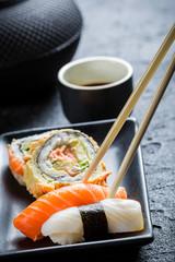 Sushi in a black ceramic eaten with chopsticks