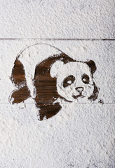 Panda figure made of sugar powder on wooden background