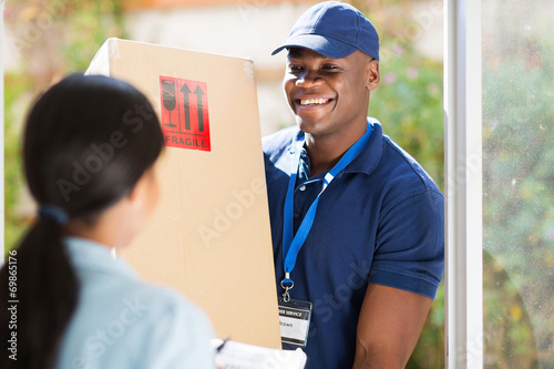 young african american delivery man delivering a package - 69865176