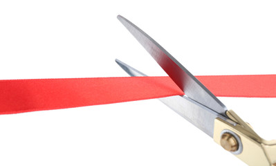 Scissors cutting red ribbon isolated on white