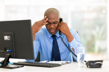 stressed businessman talking on landline phone