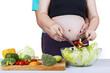 Closeup of pregnant woman making salad