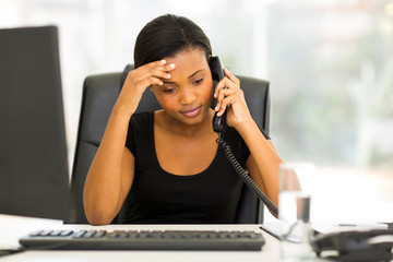 tired black businesswoman using landline phone