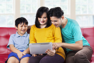 Happy family using digital tablet on couch