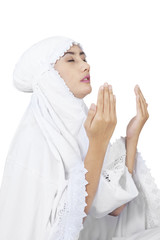 Muslim wearing white dress praying