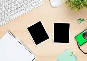 Photo frames on office table with notepad, computer and camera