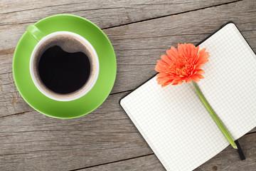 Blank notepad, coffee cup and orange gerbera flowers