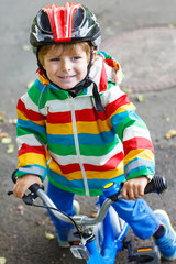 Adorable kid boy in red helmet and colorful raincoat riding his