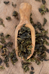 dried green tea on wooden surface