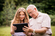 Grandchild shows grandfather tablet