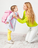 Fototapety Mother helps her daughter get ready for school