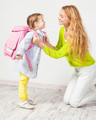 Mother helps her daughter get ready for school