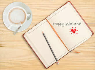 """Happy weekend"" on notebook with pencil and coffee cup on wooden"