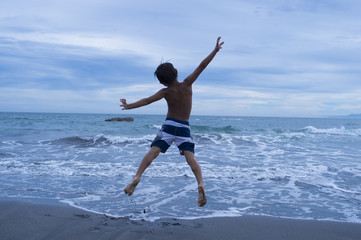 Boy to jump in the water's edge