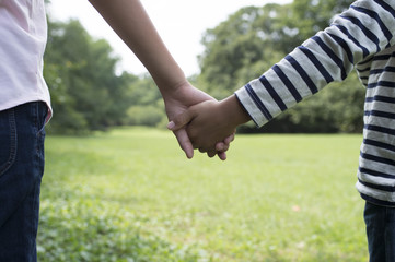 Children holding hands in field