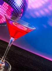 red cocktail with sparkling disco ball background