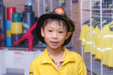 little Asian boy in firefighter uniform
