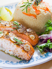 Roasted salmon fish with garlic fresh lettuce and couscous