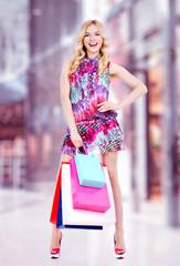 Happy young woman with colorful shopping bags.