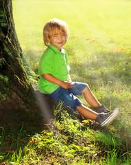 Boy sits near tree