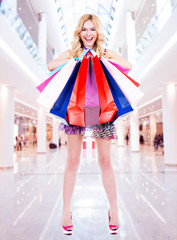 Happy blonde woman with colorful shopping bags.
