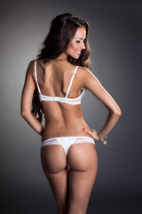 Rear view of smiling tanned model in lingerie