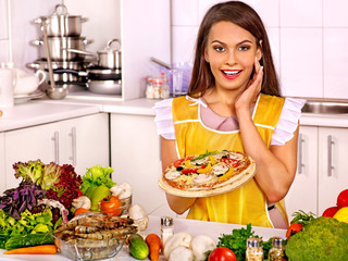 Woman cooking pizza.