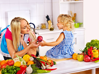 Mother and child cooking at kitchen.