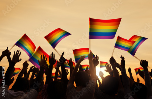 Silhouettes of People Holding Gay Pride Symbol FLag - 69873128