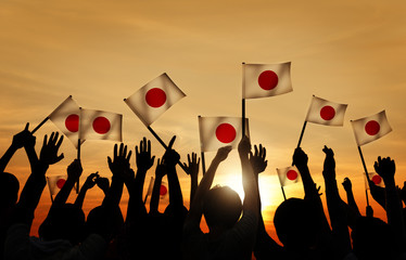 Silhouettes of People Holding the Flag of Japan