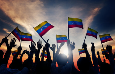 Group of People Waving Venezuelan Flags in Back Lit
