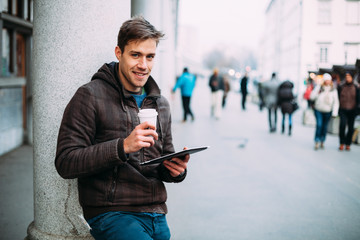 Young man drinking coffee on street using tablet computer