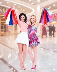Smiling women raised up colorful shopping bags.