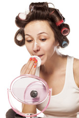 young woman with curlers removes makeup