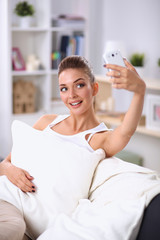 Happy brunette taking a photo of herself with her mobile phone