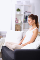 Woman sitting on the couch in  living room and smiling