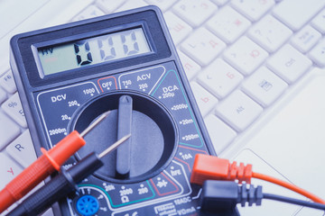 multimeter on the white laptop. close-up