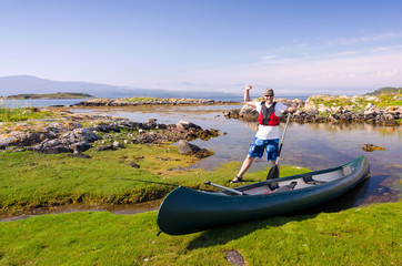 Happy canoe angler in wild nature